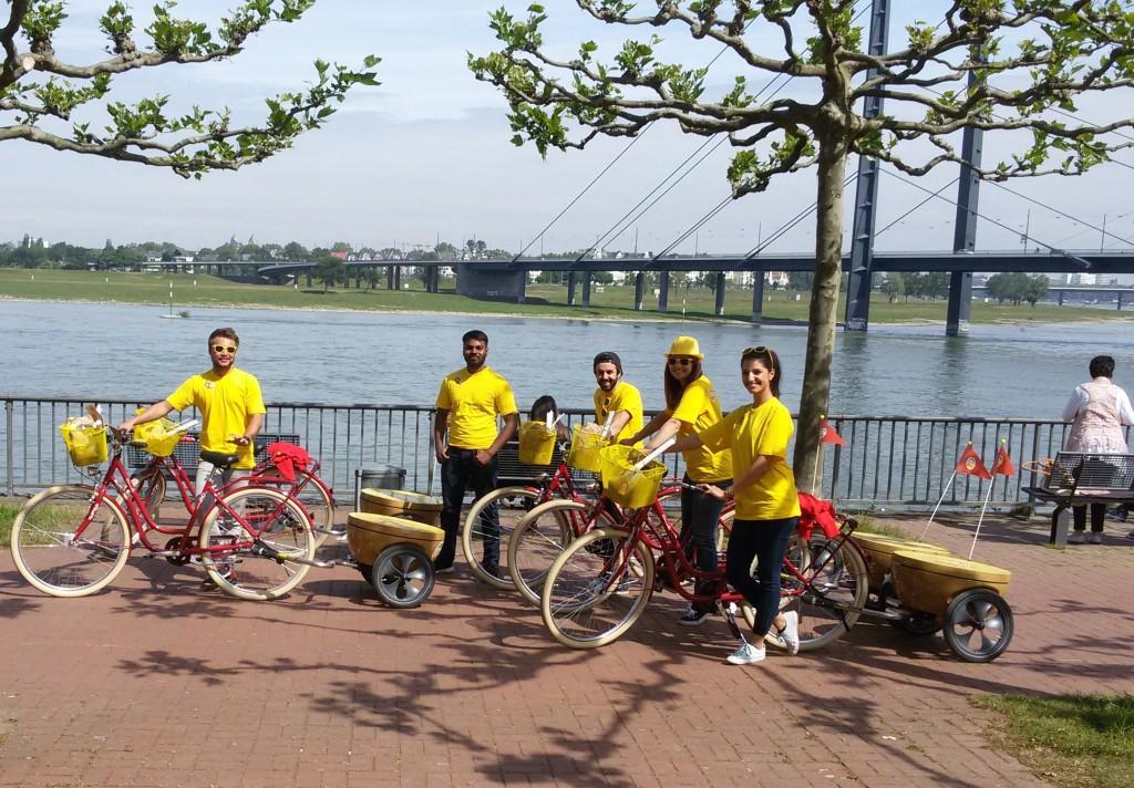 Promoter/innen mit Fahrrädern mit Anhänger in Kiwiform am Rhein in Düsseldorf