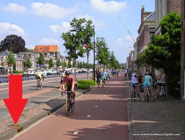 Abfluss ohne Einschränkung der nutzbaren Radwegbreite in den Niederlanden. (Foto mit freundlicher Erlaubnis von David Hembrow, A view from the cyclepath, CC-BY-NC-SA, Pfeil von Peter Maier)