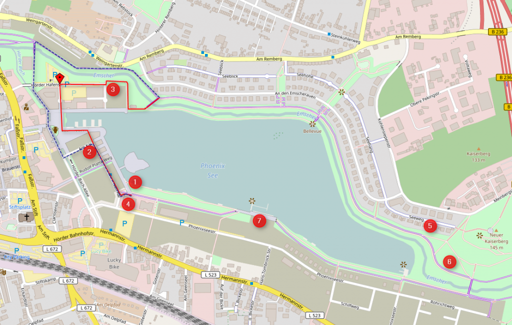 Der Bereich am Westrand des Sees zwischen Wasser und der roten Linie ist reine Fußgängerzone, die übrigen Fußgängerflächen (hellblau) sind freigegeben. Es gibt zwei Möglichkeiten, die reine Fußgängerzone zu umfahren . Beide (auf der Karte blau und rot eingezeichnet) sind unbeschildert, für Ortsunkundige nicht zu erkennen und können nur als Notlösung bezeichnet werden. Den grundlegenden Fehler bei der Planung des Sees können sie nicht heilen. (Karte: Open-Streetmap-Mitwirkende/Peter Maier , CC-BY-SA)